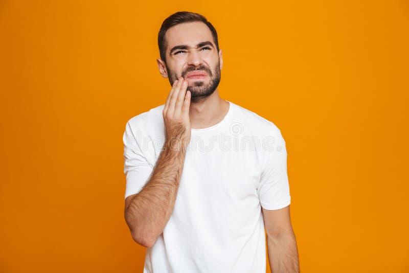 Imagem do homem unshaved 30s no t-shirt que toca em seu mordente e que sofre da dor de dente quando, sobre o fundo amarelo imagem de stock