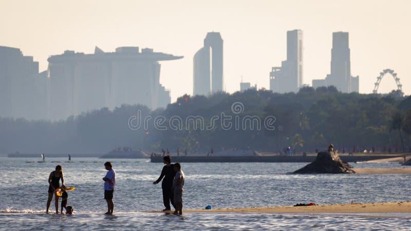 Imagem do lazer da praia do enjoysthe dos povos com construções do distrito central de Singapura imagem de stock royalty free