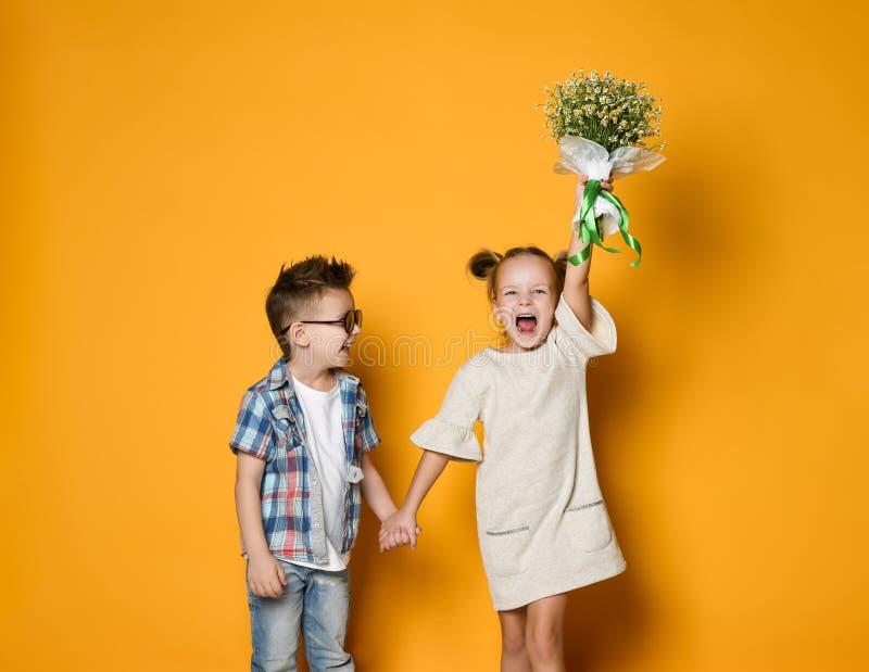 A imagem do menino caucasiano feliz novo d? flores a sua amiga isolada sobre o fundo amarelo imagem de stock
