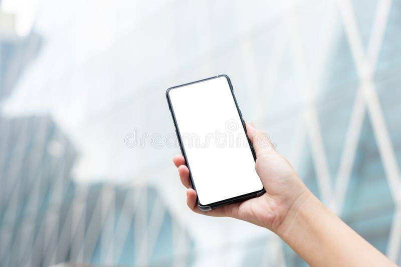 Imagem do modelo da m?o da mulher que guarda smartphones m?veis a tela branca isolada para o projeto e o outro do modelo fundo de fotografia de stock royalty free