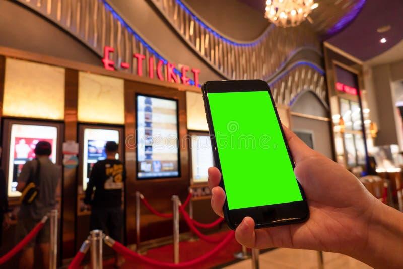 Imagem do modelo da mão da mulher que guarda a tela branca dos smartphones móveis para o projeto e o outro do modelo fundo de exp foto de stock