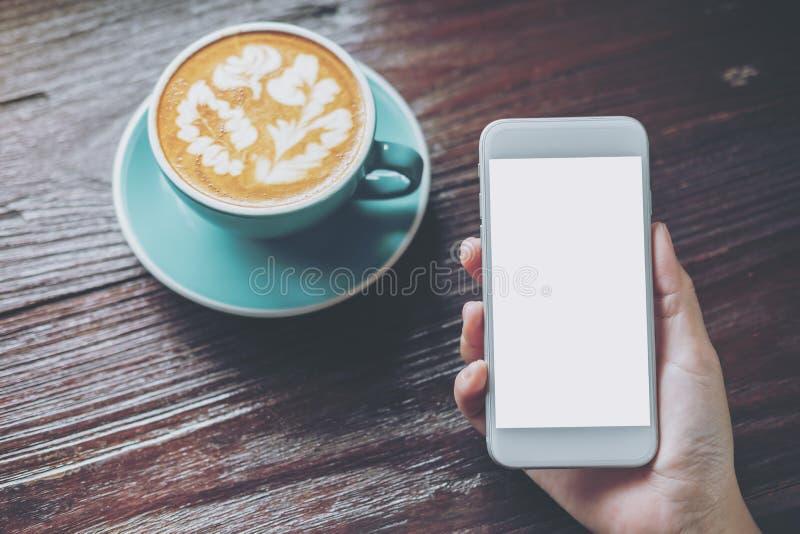Imagem do modelo da mão que guarda o telefone celular branco com a tela vazia com o copo de café quente azul na tabela de madeira imagem de stock