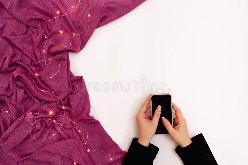 Imagem do modelo da mão do ` s da mulher que guarda o telefone celular com a tela vazia no fundo branco com o lenço no café moder foto de stock