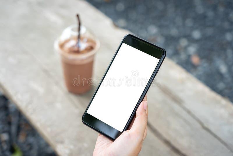 Imagem do modelo da m?o da mulher que guarda a tela branca dos smartphones m?veis para o projeto e o outro do modelo fundo de exp foto de stock