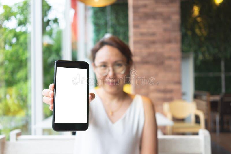 Imagem do modelo da m?o da mulher que guarda a tela branca dos smartphones m?veis para o projeto e o outro do modelo fundo de exp imagens de stock