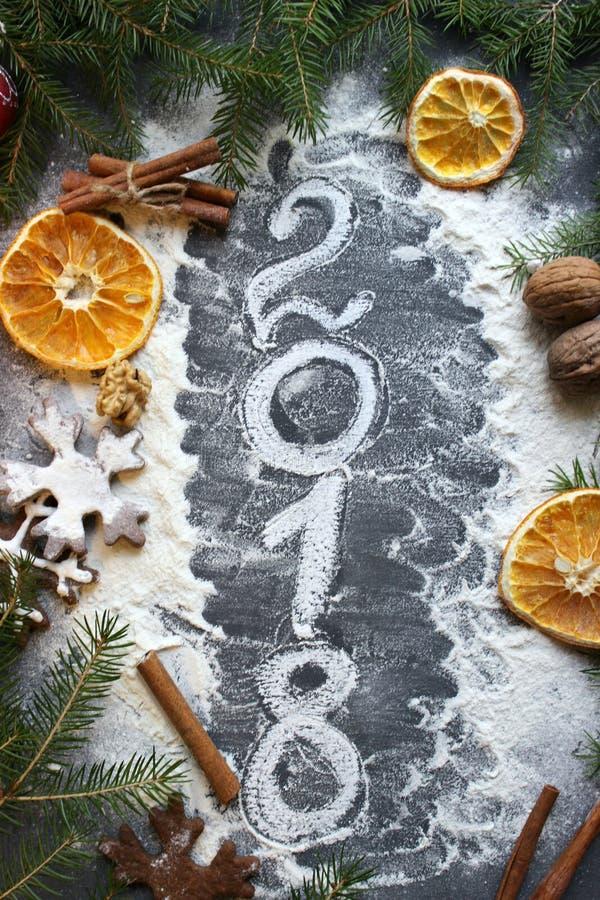 A imagem do Natal, numeral 2018 é escrita com farinha em um fundo escuro imagem de stock