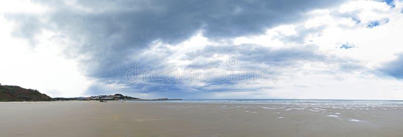 Imagem do panorama de uma praia ou de uma baía no Oceano Atlântico com areia, ondas e um céu azul com as nuvens bonitas no verão fotos de stock