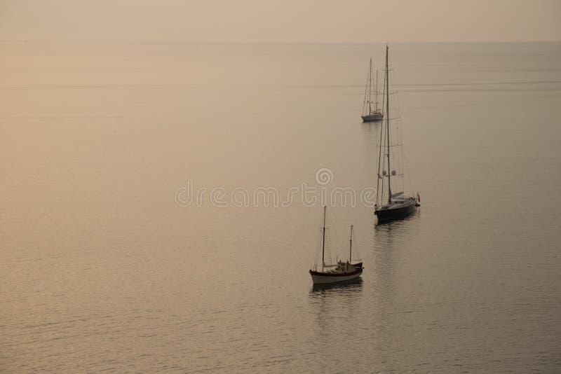 Imagem do por do sol dourado bonito no fundo da parada do iate Silhueta de barcos de navigação na baía no mar de Andaman imagem de stock