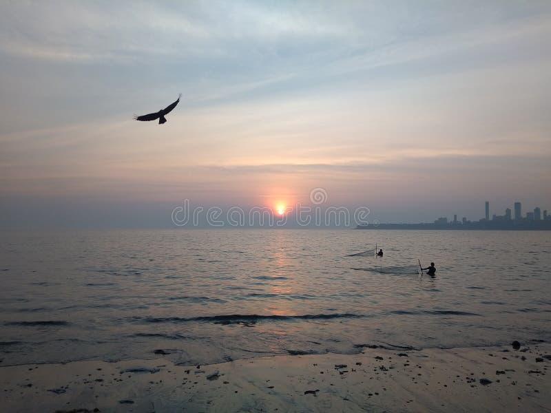 Imagem do por do sol em nivelar a cara do mar fotografia de stock