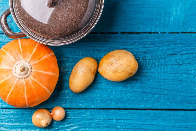 Imagem do potenciômetro com tampa, batatas, abóbora, cebolas fotografia de stock royalty free