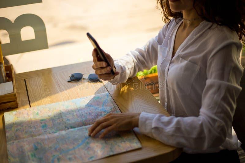 Imagem do quadro das mãos das mulheres que guardam um telefone celular, telefone celular dos usos no café, acima do mapa de papel fotos de stock royalty free