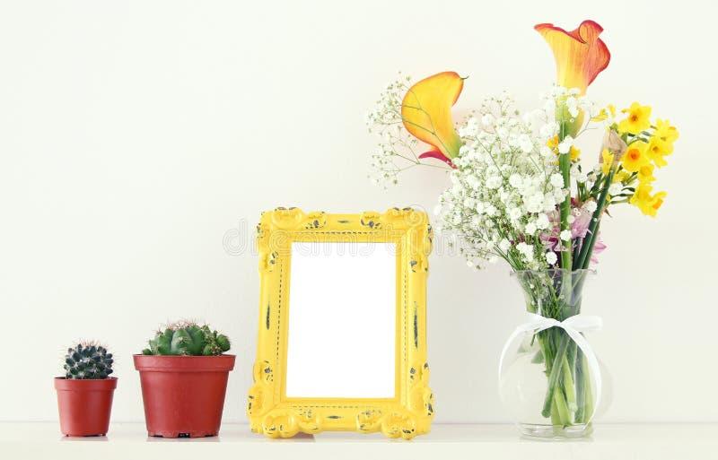 A imagem do ramalhete bonito da mola amarela floresce ao lado do quadro vazio da foto do vintage sobre a tabela branca Para a zom imagens de stock