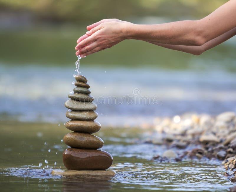 A imagem do sumário do close-up da água de derramamento da mão da mulher em tamanhos diferentes desiguais marrons naturais áspero imagens de stock