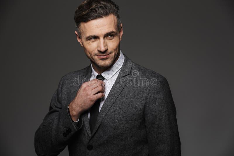 Imagem do terno de negócio vestindo do homem unshaved maduro que olha de lado imagens de stock