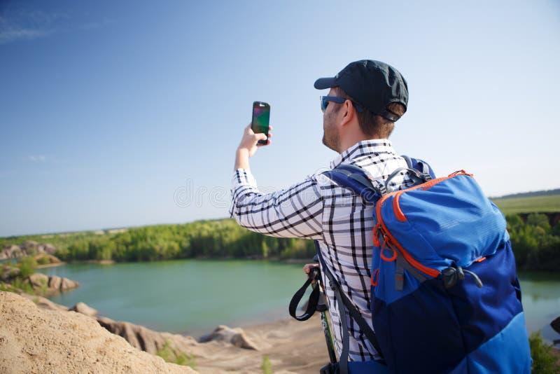 Imagem do turista com trouxa que fotografa no monte imagem de stock