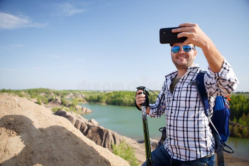 Imagem do turista com trouxa que fotografa no monte imagens de stock