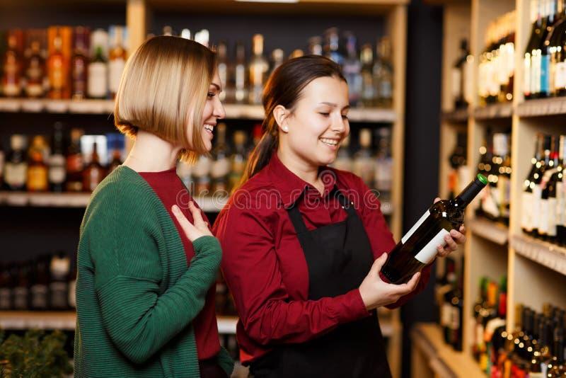 Imagem do vendedor e do comprador no fundo borrado das cremalheiras com as garrafas do vinho fotografia de stock