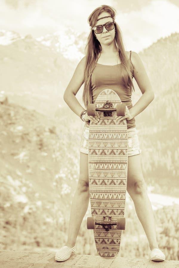 Imagem do vintage da menina nova e bonita da hippie com skate imagens de stock