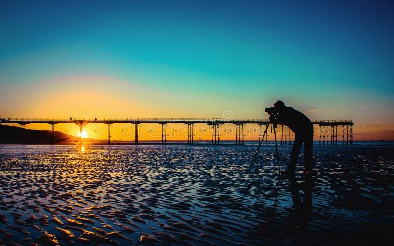 Imagem do vintage da silhueta de um fotógrafo na praia fotografia de stock royalty free