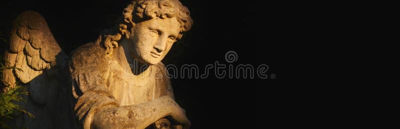 Imagem do vintage de um anjo triste em um cemitério na sombra fotos de stock