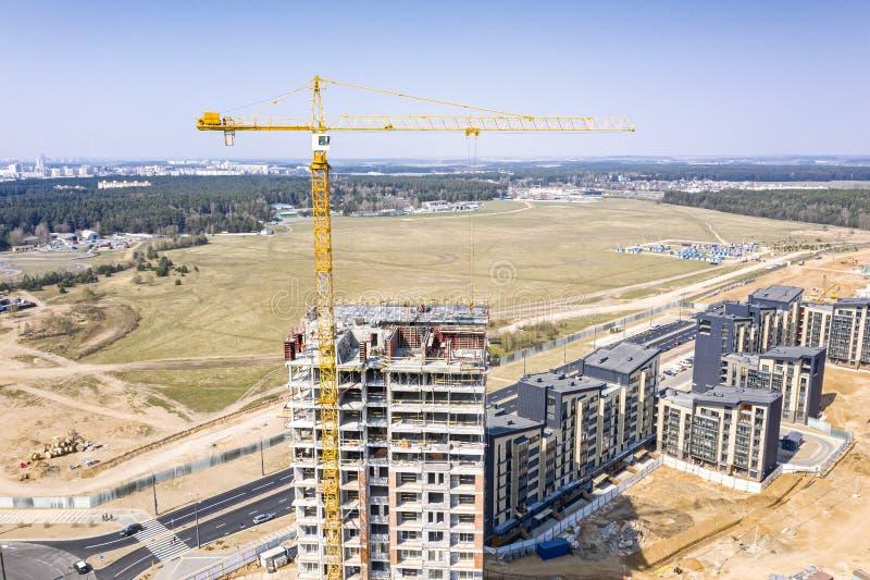 Imagem do zangão do canteiro de obras da cidade com o guindaste de torre industrial amarelo fotos de stock royalty free