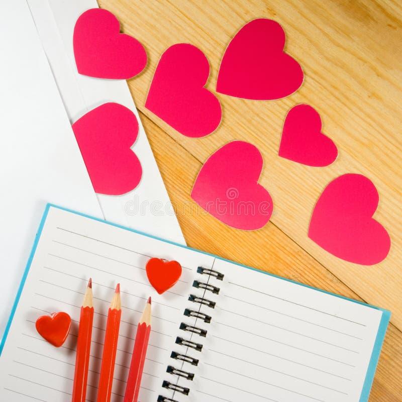 imagem dos envelopes, dos cadernos, dos lápis, e dos corações do papel em um close-up de madeira da tabela imagens de stock royalty free