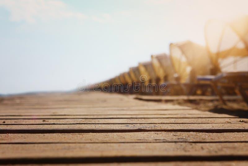 Imagem dos feriados da plataforma de madeira em cadeiras de praia tropicais sob guarda-chuvas Curso do ver?o e conceito das f?ria fotografia de stock royalty free