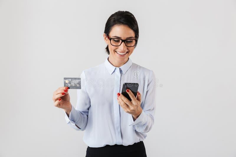 Imagem dos monóculos vestindo da mulher nova do escritório que guardam o cartão do telefone celular e de crédito, isolada sobre o imagens de stock