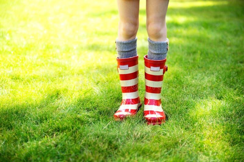 Imagem dos pés da criança que desgastam carregadores de chuva vermelhos imagens de stock royalty free