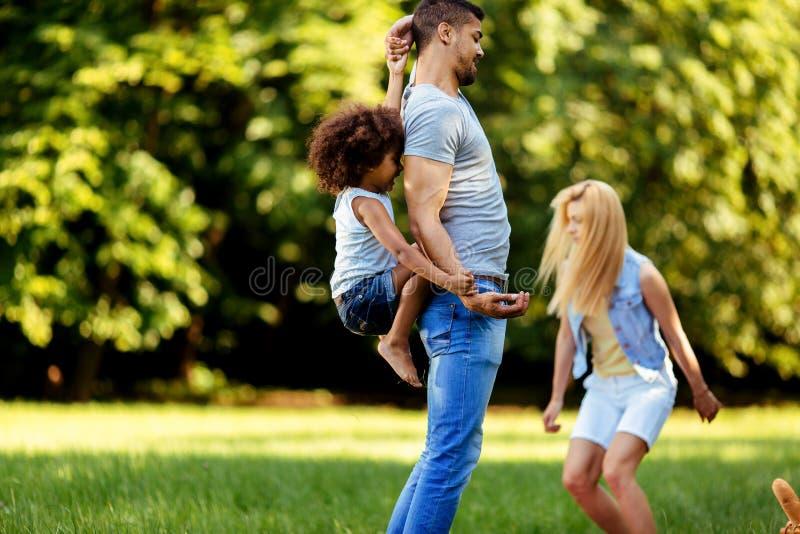Imagem dos pares novos felizes que passam o tempo com sua filha imagens de stock royalty free