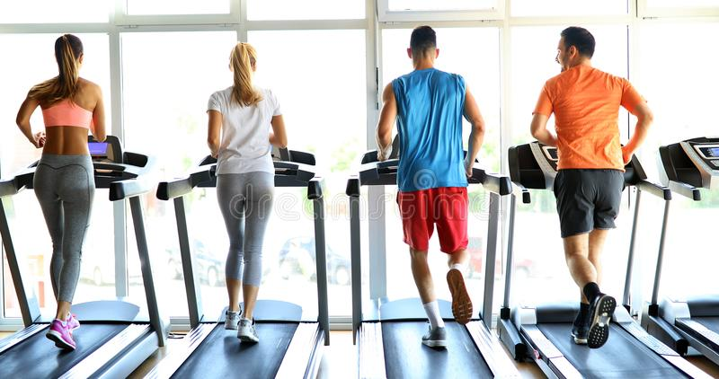 Imagem dos povos que correm na escada rolante no gym fotos de stock