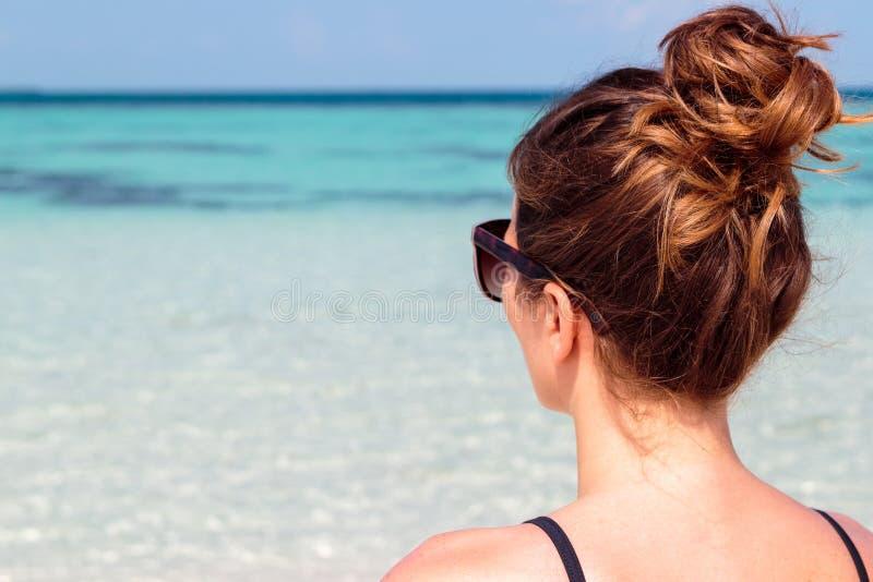 Imagem dos três quartos de uma jovem mulher na praia que olha o mar azul claro imagens de stock