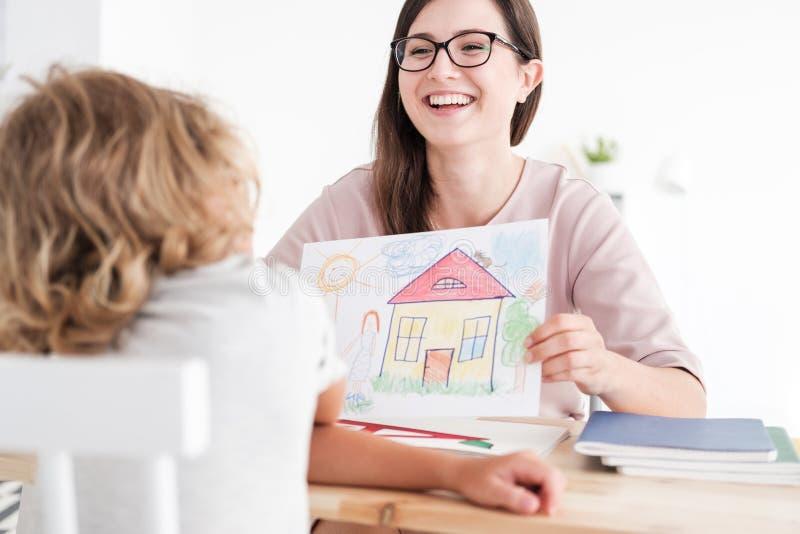 Imagem e criança de sorriso do psicólogo em um centro de apoio da família imagens de stock royalty free