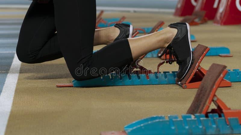 Imagem embalada ação de um atleta fêmea que deixa os blocos começar foto de stock royalty free
