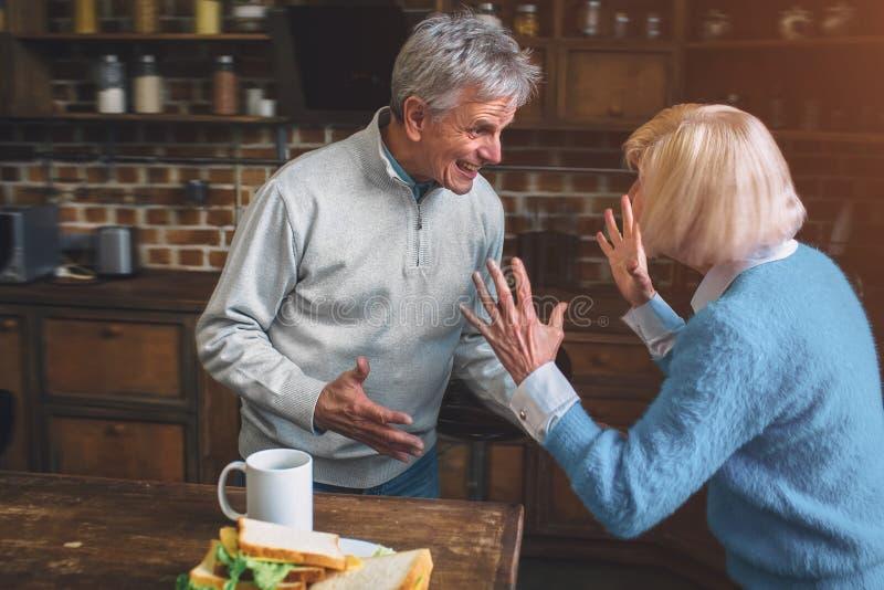 Imagem engraçada da avó idosa que está com o vovô e o talki imagem de stock
