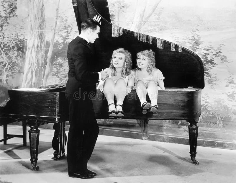 Imagem engraçada dos gêmeos que sentam-se dentro de um piano que fala a um homem novo (todas as pessoas descritas não são um vivo foto de stock royalty free