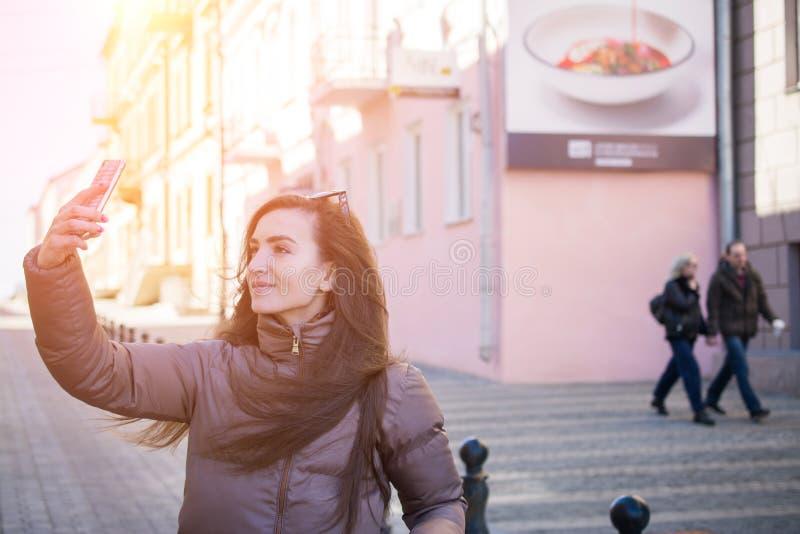 Imagem exterior do estilo da rua da mulher na moda nova que faz o selfie na rua da cidade imagens de stock royalty free