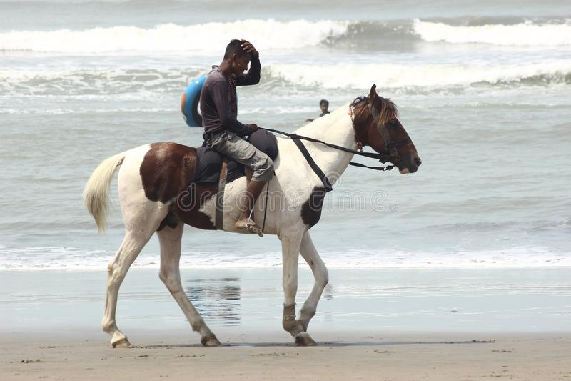 A imagem foi tomada de um homem que a imagem guarda um homem que monta um cavalo pelo mar em Bangladesh Cox& x27; feira de s imagem de stock