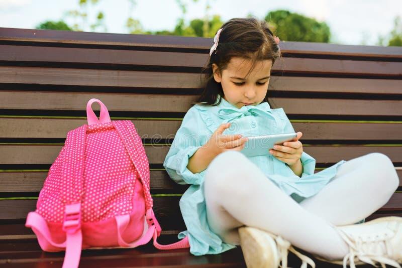 Imagem horizontal da menina brincalhão da criança que joga com o smartphone que senta-se no banco no parque da cidade Tecnologia, foto de stock