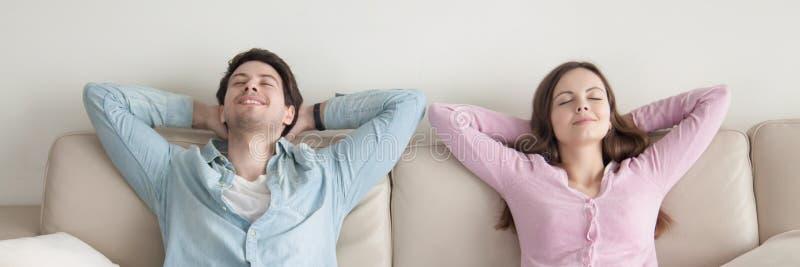 Imagem horizontal dos pares com os olhos fechados que descansam no sofá fotografia de stock royalty free