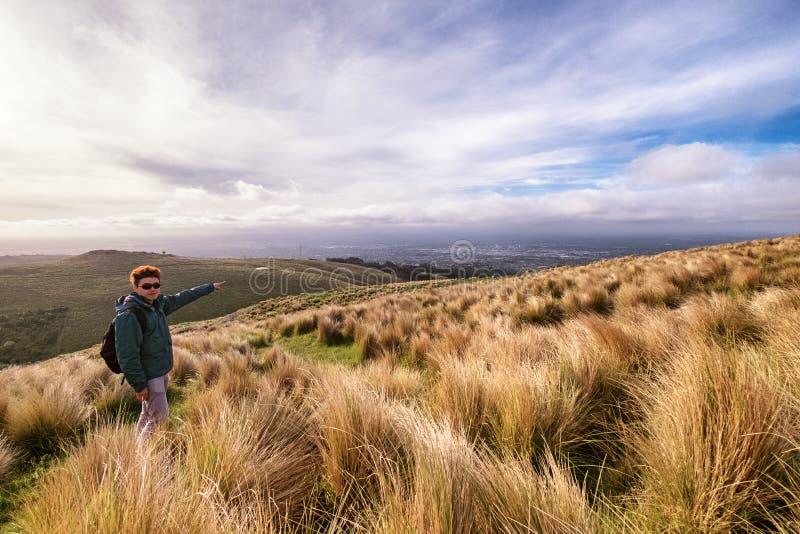 Imagem inspirada de um homem que alcança a parte superior da montanha que negligencia Christchurch, Nova Zelândia foto de stock
