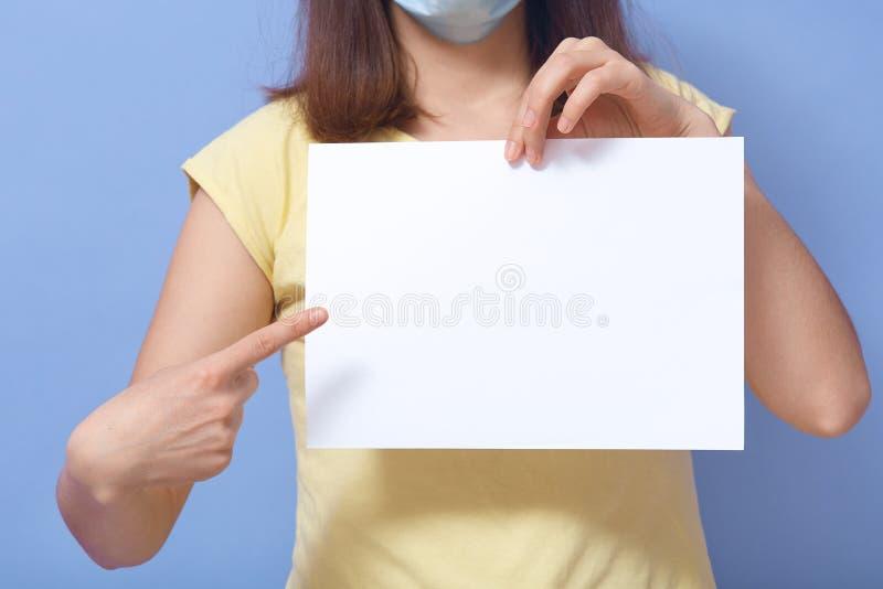 Imagem interior de uma jovem desconhecida usando máscara antibacteriana, segurando uma folha de papel em branco, fazendo gestos,  foto de stock