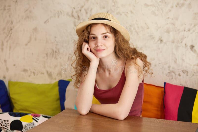Imagem interna do assento fêmea positivo atrativo no sofá, pondo seus braços sobre a tabela, tocando na cara com a uma mão, olhan fotografia de stock