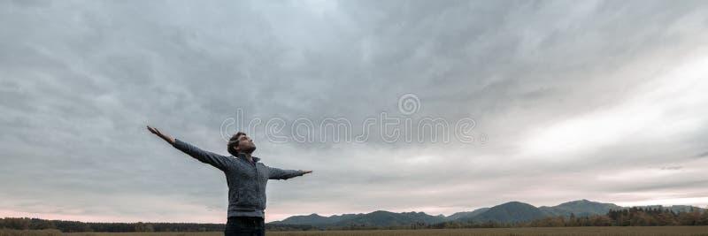 Imagem larga da vista do homem novo que comemora a vida foto de stock