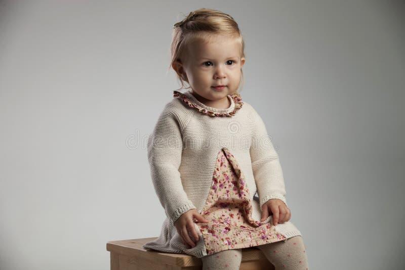 Imagem lateral de um sorriso assentado do bebê imagem de stock