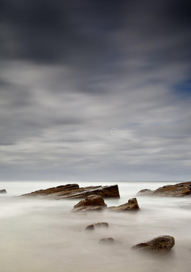 Mar e rochas enevoados foto de stock