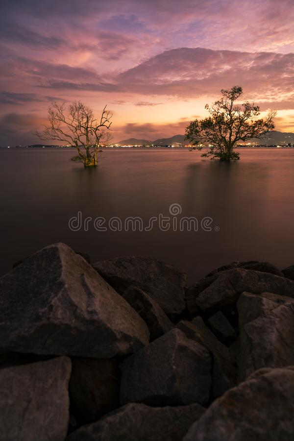 Imagem longa da exposição do seascape dramático do céu com a rocha na opinião da natureza da paisagem do cenário do por do sol imagens de stock royalty free