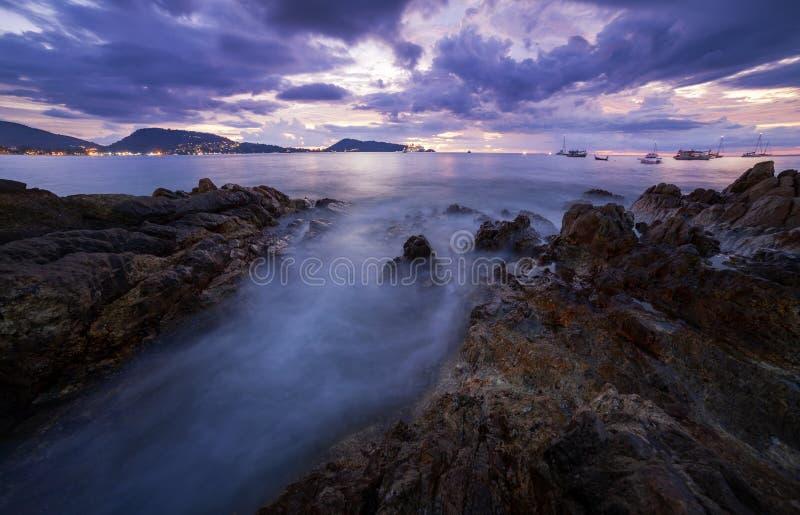 Imagem longa da exposição do seascape dramático do céu com a rocha no cenário do por do sol, na paisagem bonita e na luz da natur fotografia de stock royalty free
