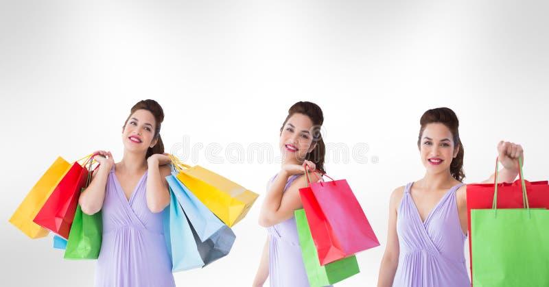 Imagem múltipla da mulher que mantém sacos de compras contra o fundo branco foto de stock