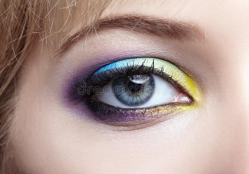 Imagem macro do close up do olho fêmea humano com violeta, o azul e imagens de stock royalty free